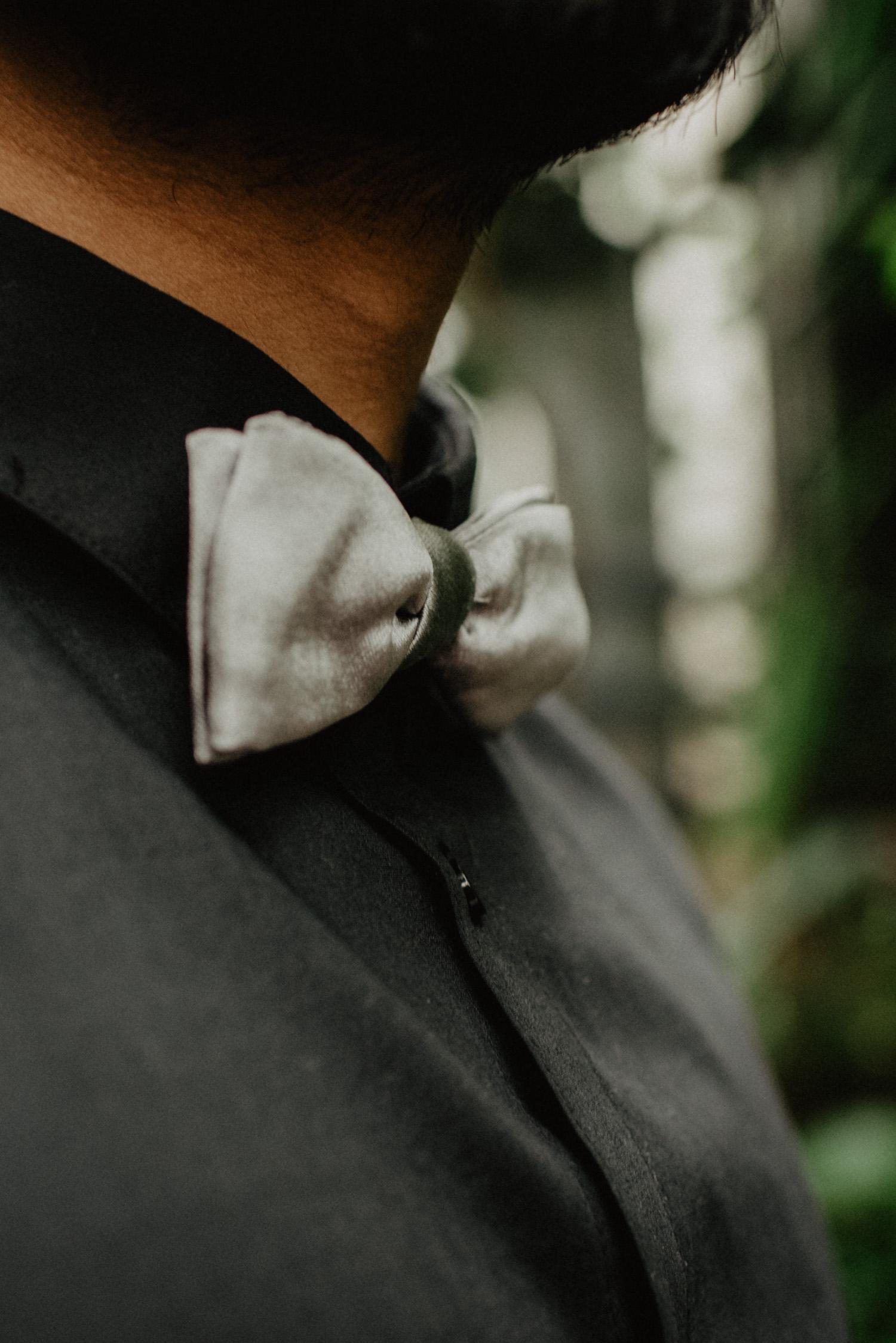 Detailfoto des Bräutigams. Es ist ein schwarzes Hemd mit einer grauen Fliege zu sehen.