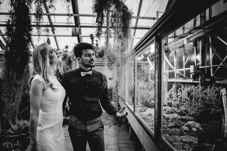 Ein Brautpaar sieht sich Hängepflanzen in einem Gewächshaus an.