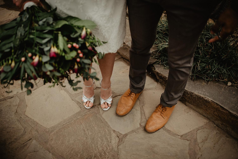 Detailfoto der Füße des Brautpaares. Sie hat ein kurzes Kleid und silberfarbene High Heels an, er eine dunkelgraue Stoffhose und hellbraune Anzugschuhe.