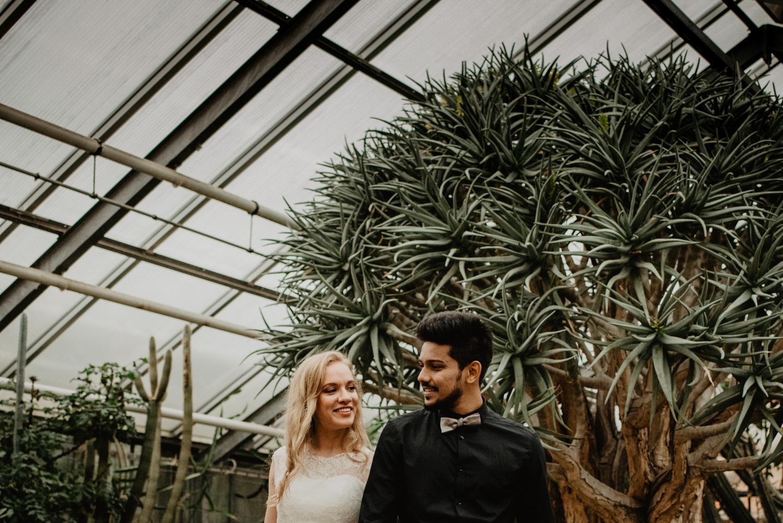 Ein multikultturelles Brautpaar, fotografiert ab dem Rumpf aufwärts und mit mediterranen Pflanzen im Hintergrund.
