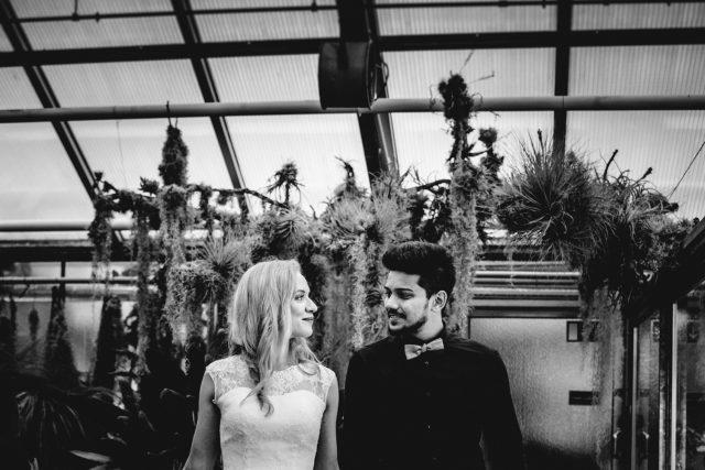 Ein Brautpaar steht in einem gewächshaus und schaut sich gegenseitig seitlich an.