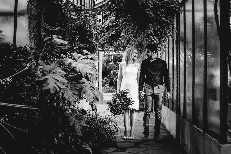Ein Brautpaar bei einem Elopement-Shooting in Bonn ist umgeben von Pflanzen.