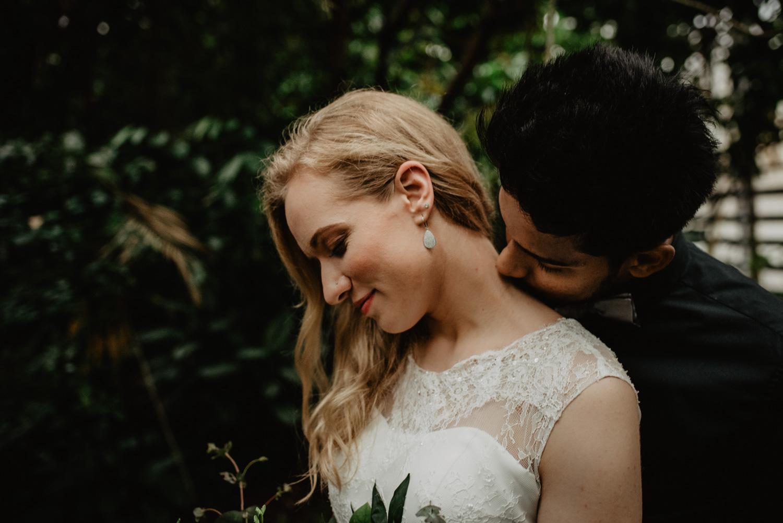 Ein Mann steht hinter seiner Braut und küsst sie am Hals. Sie hält einen Blumenstrauß und ihre langen blonden lockigen Haare liegen auf einer Seite.