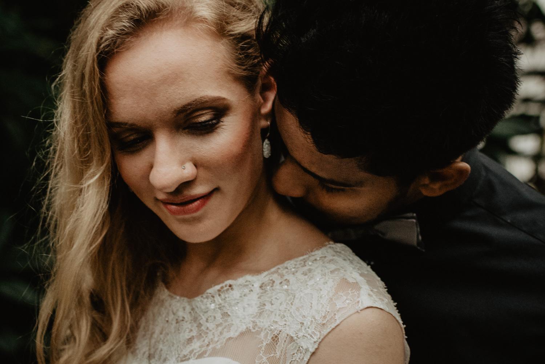 Ein Mann steht hinter seiner Braut und küsst sie am Hals. Ihre langen blonden lockigen Haare liegen auf einer Seite.