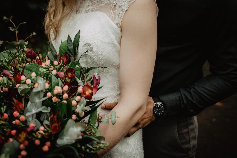 Ein Bräutigam umarmt seine Braut von hinten, während sie einen Boho-Blumenstrauß in den Händen hält.