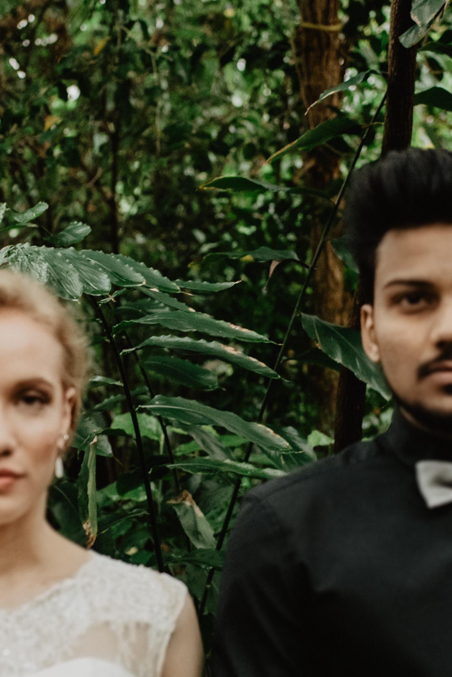 Ein Brautpaar steht frontal zur Kamera und schaut ernst. Ihre Gesichter sind jeweils nur halb abgebildet und unscharf, während der Fokus auf die tropischen Pflanzen mittig hinter ihnen gerichtet ist.