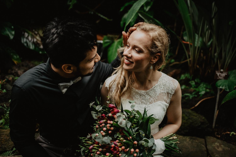 Ein Brautpaar sitzt auf einer niedrigen Mauer in einem tropischen Gewächshaus. Der Mann streicht seiner Frau die Haare aus dem Gesicht.