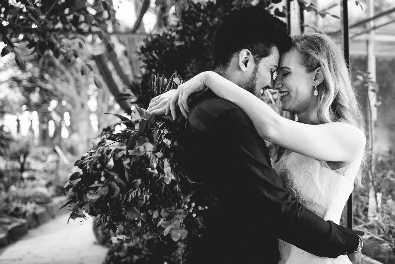Ein Brautpaar steht sich gegenüber und umarmt sich. Die Braut hat ihre Arme um den Hals des Mannes gelegt und hält dabei einen Boho-Brautstrauß in der Hand.