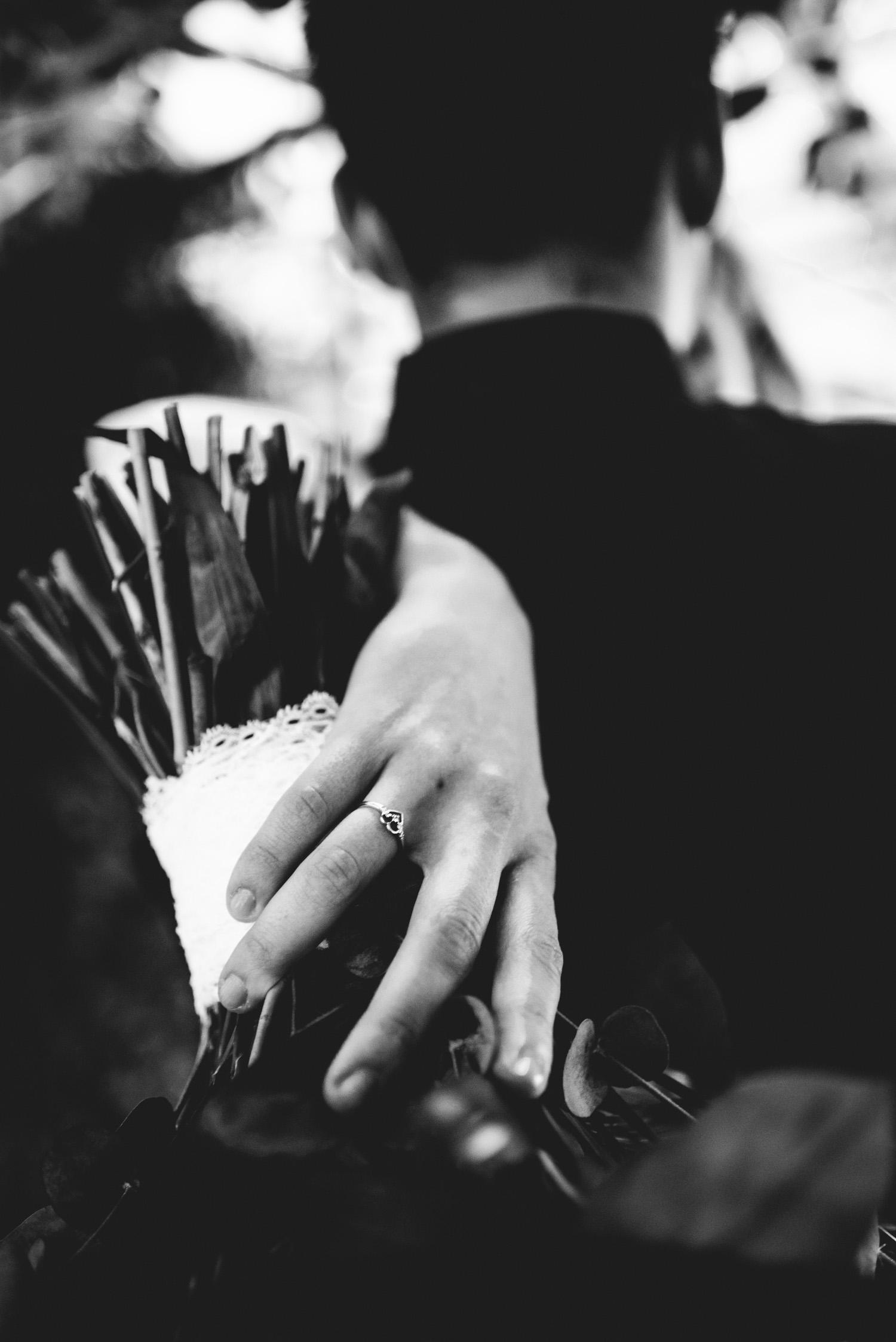 Detailfoto eines herzförmigen Eherings und einem Brautstrauß.