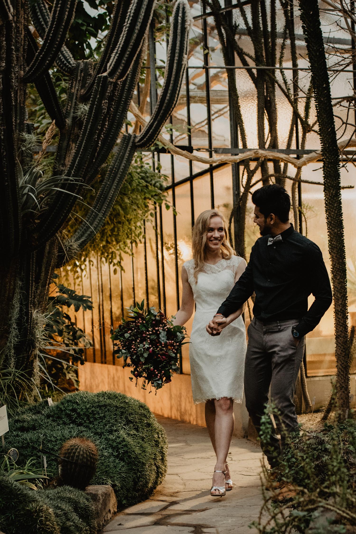 Ein Brautpaar spaziert händchenhaltend durch den botanischen Garten, während des Hochzeits-Fotoshootings.