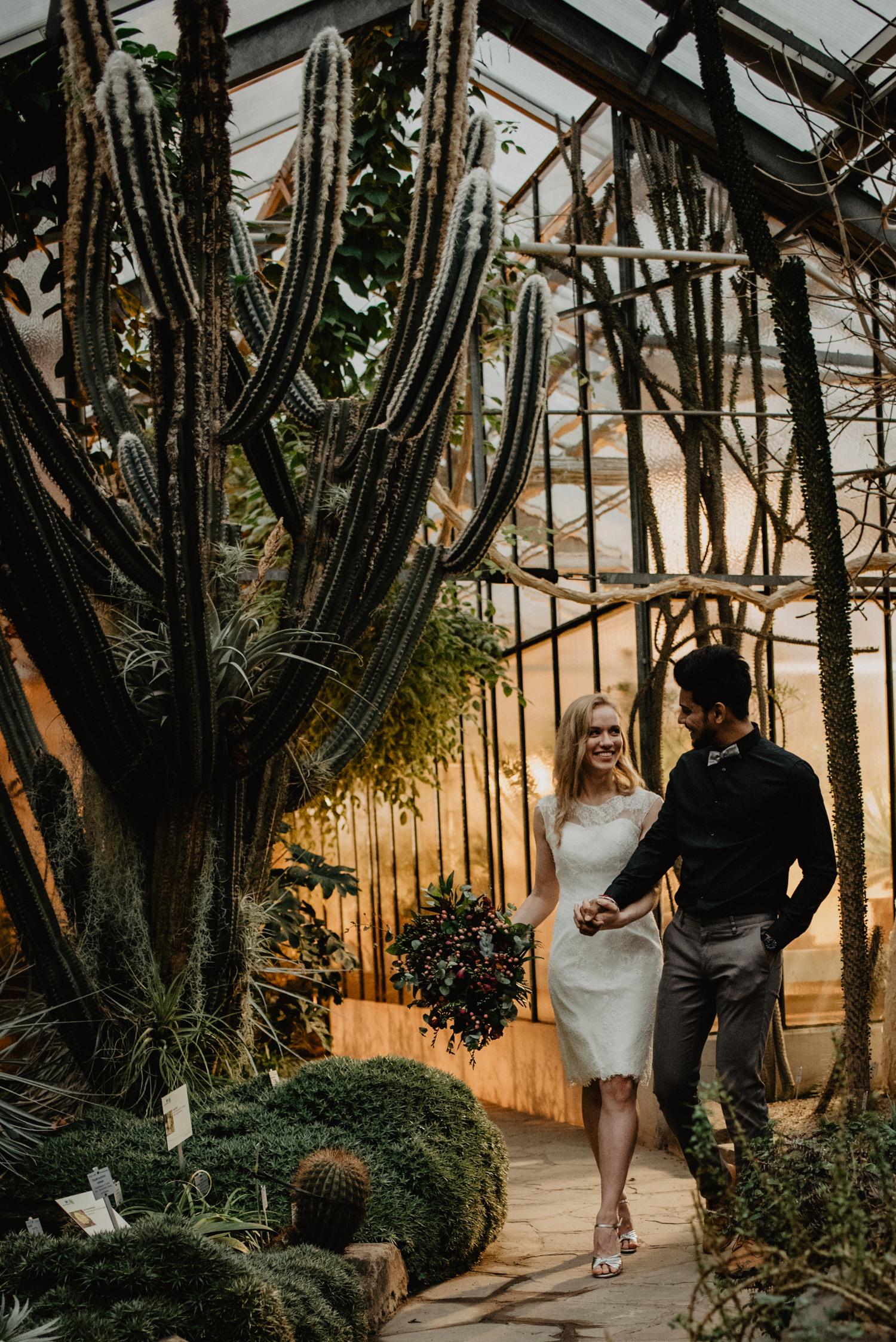 Ein Brautpaar spaziert beim Hochzeits-Fotoshooting umgeben von Wüstenpflanzen.