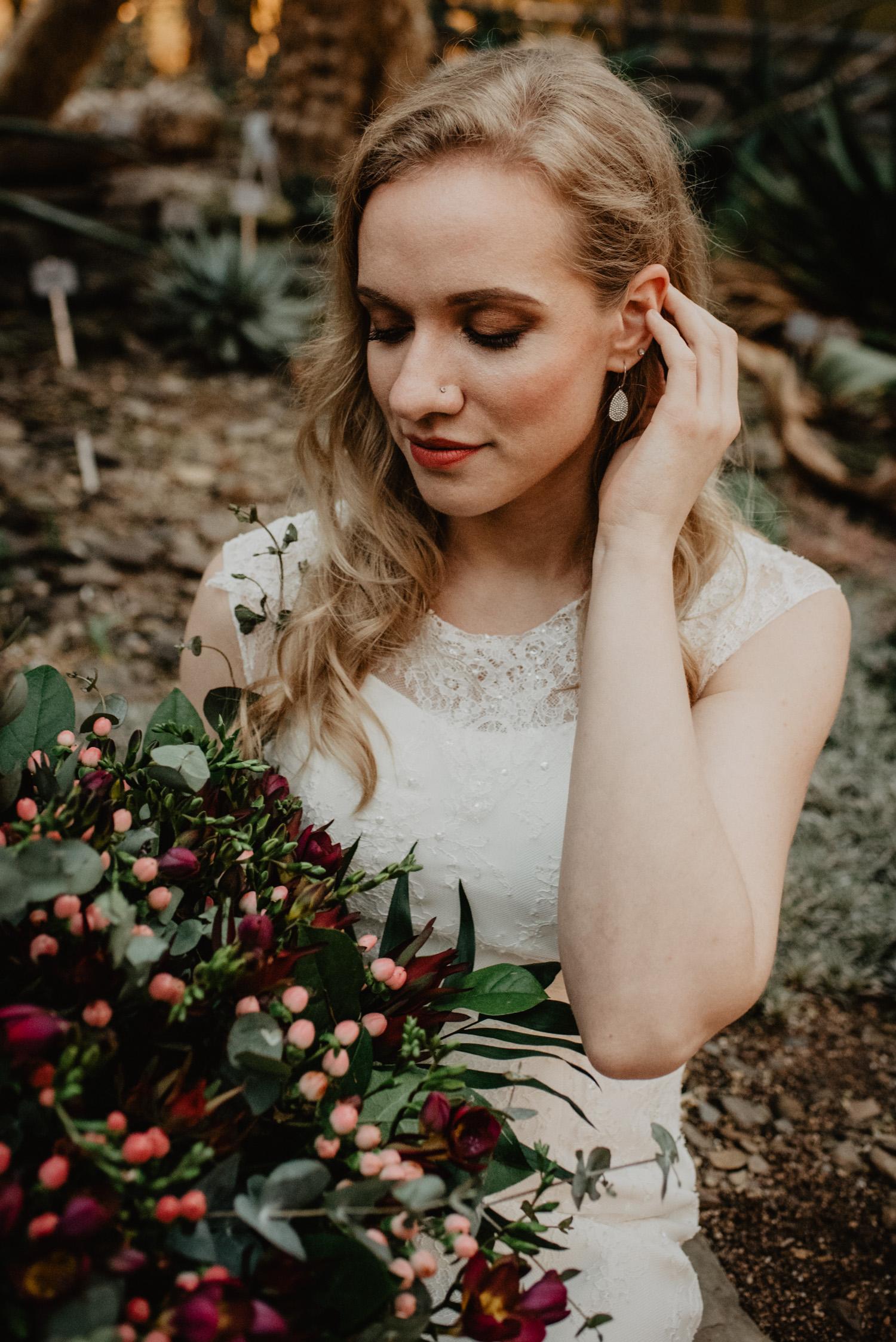 Portrait der Braut. Sie hat Smokey Eyes, lange, lockige, blonde Haare und hält einen Boho-Brautstrauß.