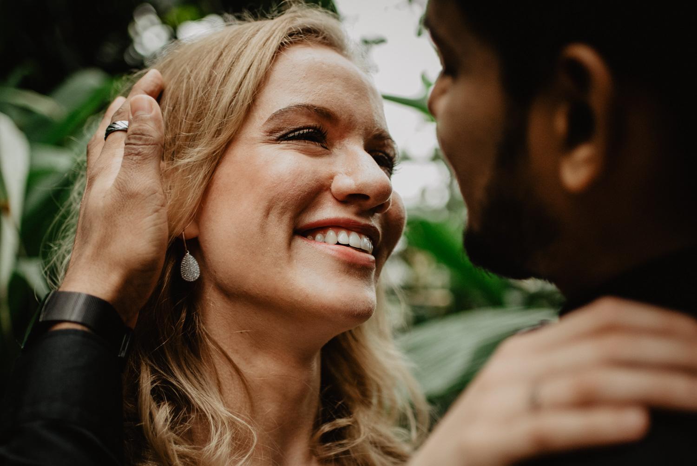 Eine blonde Braut strahlt ihren Mann beim Hochzeitsfotoshooting in Bonn an.