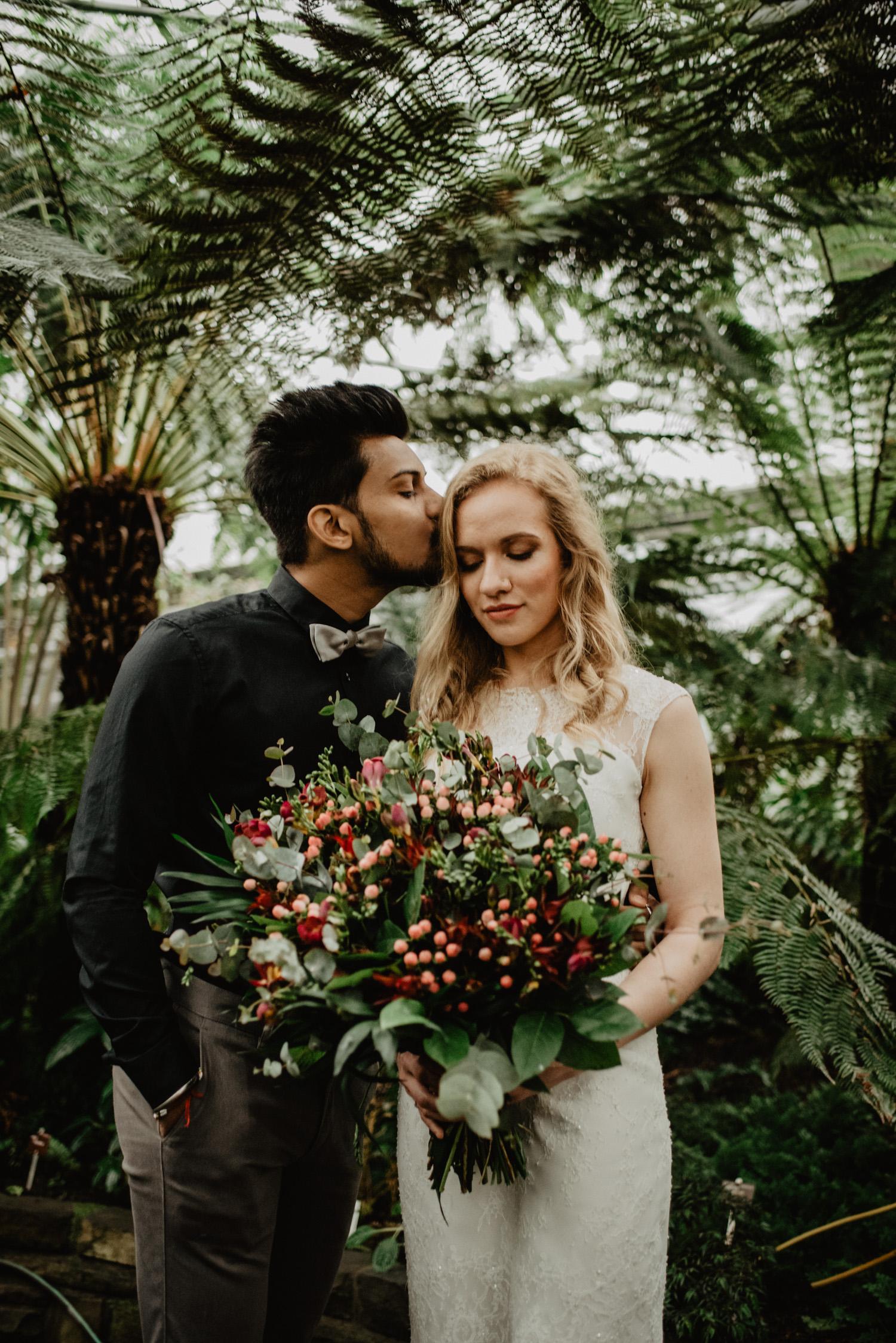 Beim Paarshooting einer multikulturellen Hochzeit küsst der Bräutigam seine Braut auf den Kopf, während sie sich ihren Boho-Brautstrauß ansieht. Das Paar steht in einem Gewächshaus.