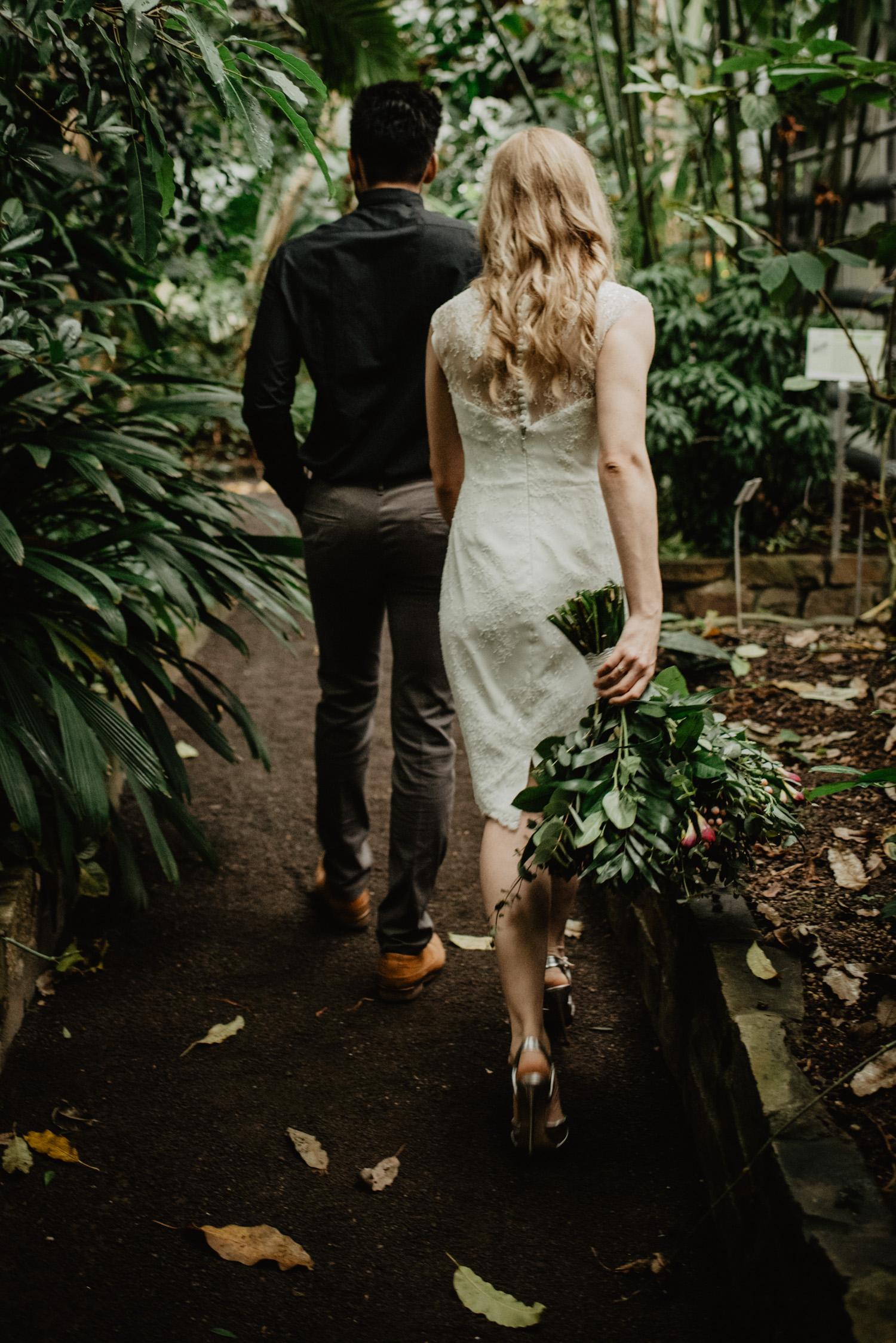 Ein Bräutigam führt seine Braut durch ein tropisches Gewächshaus in Bonn.