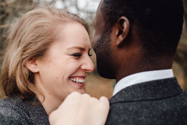 Eine Frau lehnt sich an die Schulter ihres Verlobten und lacht dabei.