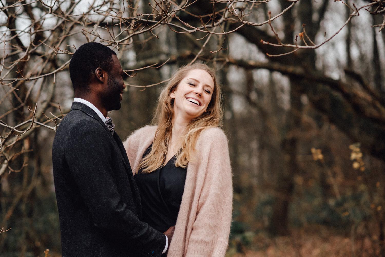 Lachendes Paar bei einem Verlobungs-Fotoshooting in einem Wald bei Düsseldorf.