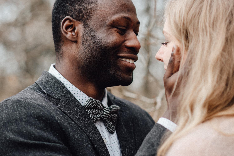 Ein Mann lächelt während er das Gesicht seiner Verlobten beim Verlobungsshooting in den Händen hält.