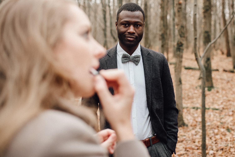 Ein Mann beobachtet lächelnd seine Frau während sie Lippenstift aufträgt.