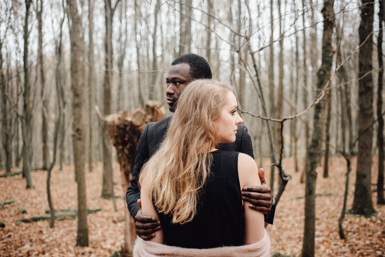 Ein Paar steht sich gegenüber in einem Wald in Düsseldorf und schaut in entgegengesetzte Richtungen.
