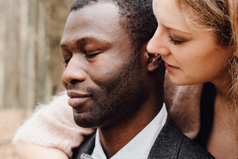 Eine blonde Frau umarmt ihren Mann von hinten und flüstert ihm etwas ins Ohr, während er lächelnd die Augen geschlossen hat.