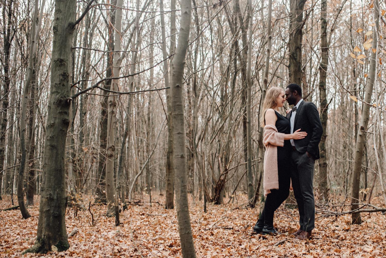 Ein Paar steht im Wald in Düsseldorf zwischen Bäumen und sieht sich verliebt an.