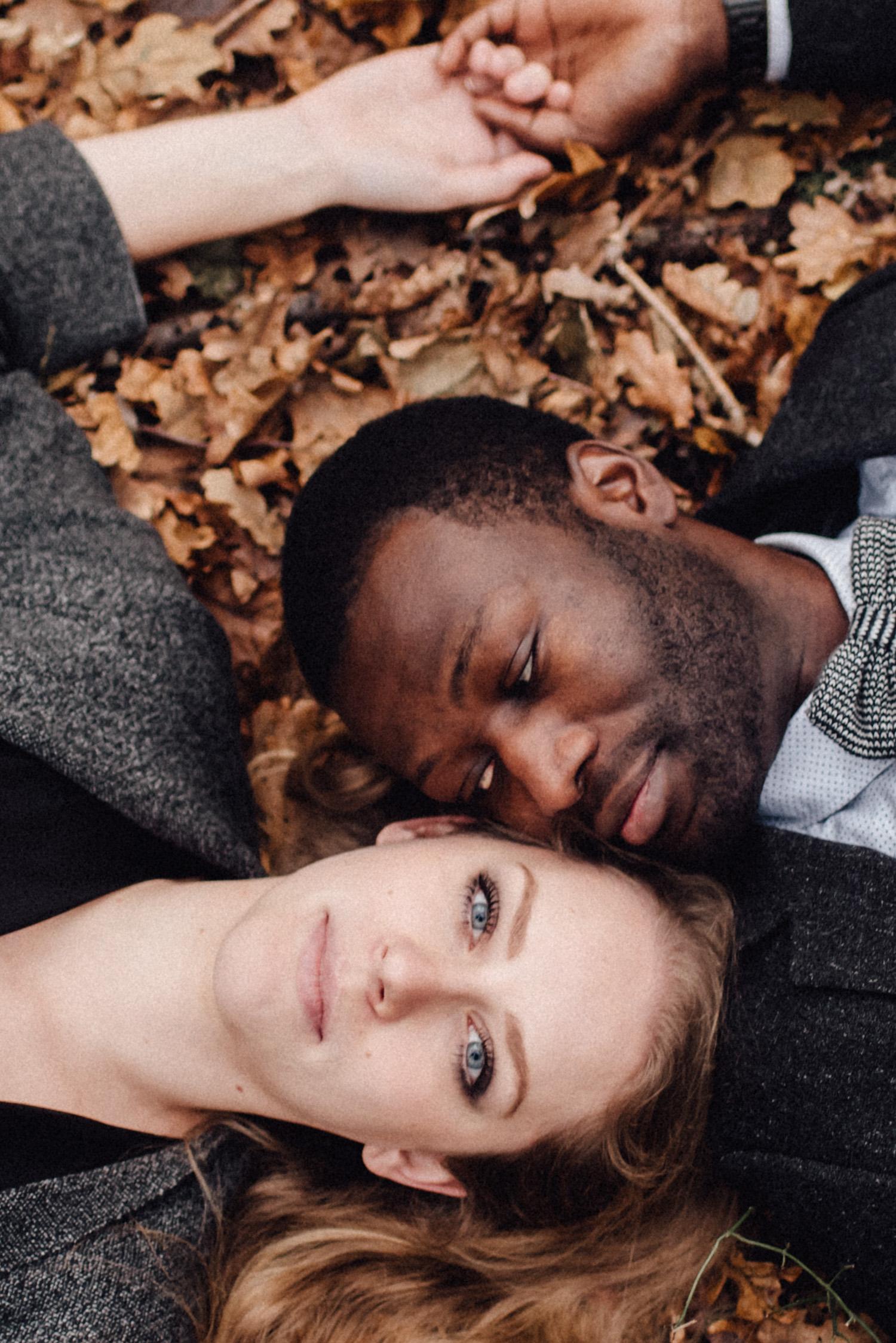 Ein Paar liegt auf einem mit Laub bedeckten Boden. Die Frau schaut den Betrachter direkt an während ihr Verlobter sie ansieht.