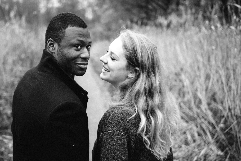 Ein dunkelhäutiger Mann schaut über die Schulter während seine blonde Verlobte ihn verliebt ansieht.