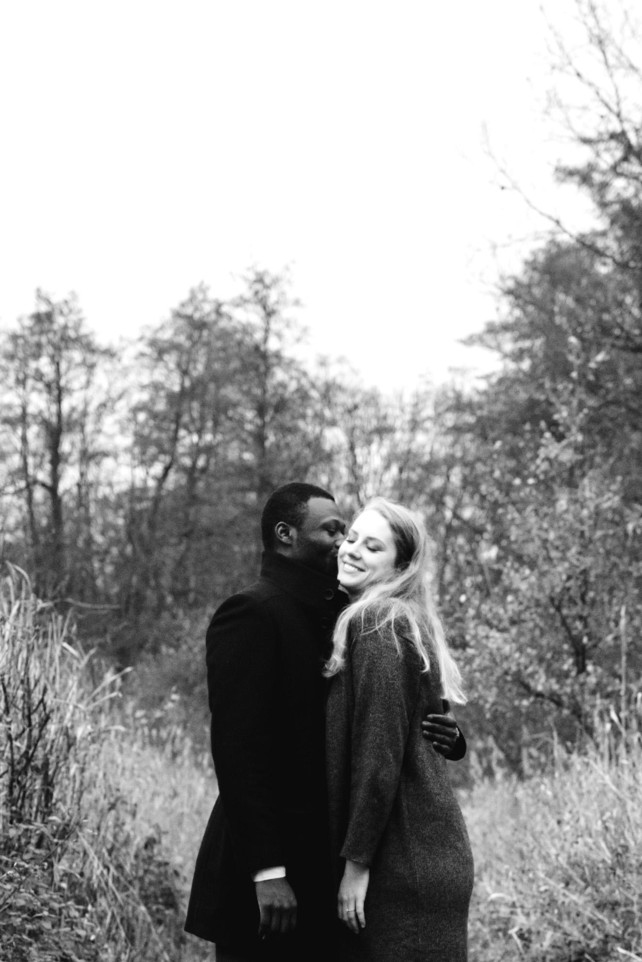 Ein Mann küsst seine lachende Verlobte auf die Wange.
