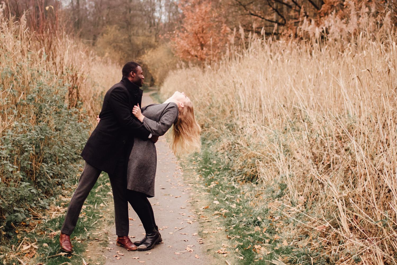 Ein Mann hält beim Spaziergang seine Freundin an der Taille und sie lässt sich lachend nach hinten fallen. Dabei fliegen ihre Haare.