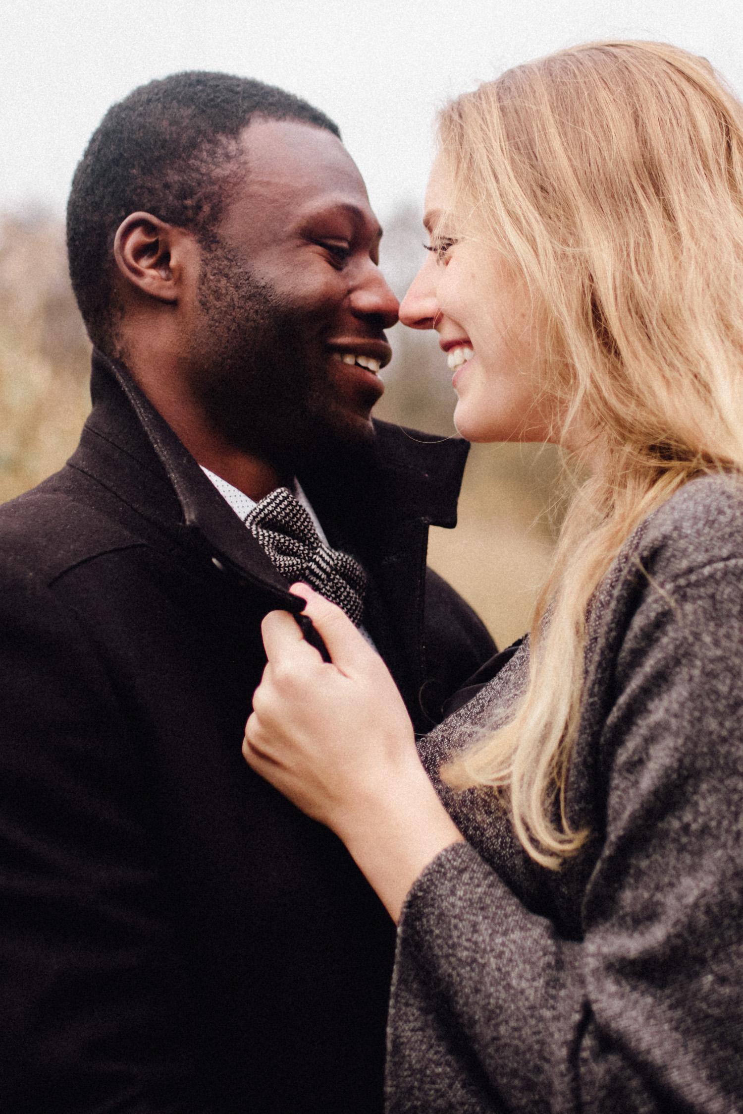Ein verliebtes multikulturelles Paar schaut sich an und lacht.