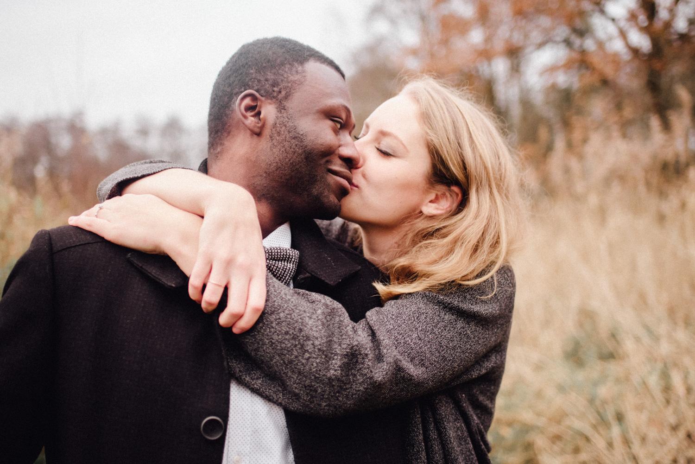 Blonde junge Frau küsst ihren Freund auf die Wange.