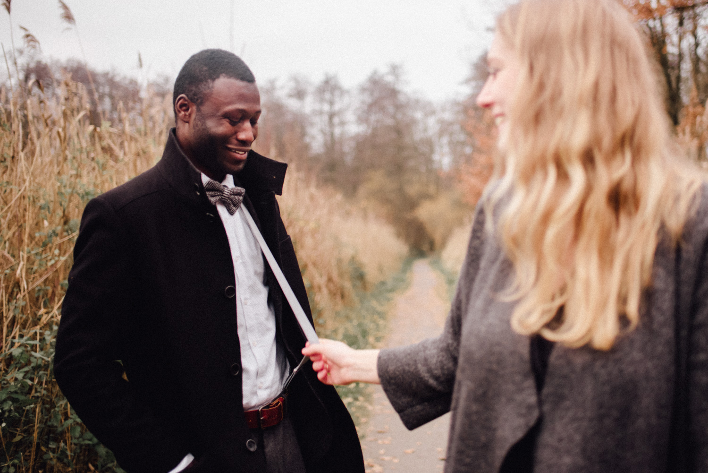 Blonde Frau spielt beim Verlobungs-Shooting in Düsseldorf mit den Hosenträgern ihres Verlobten.