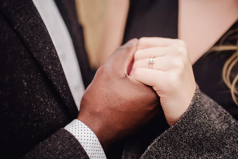 Ein Mann hält die Hand seiner Verlobten, die einen Verlobungsring trägt.