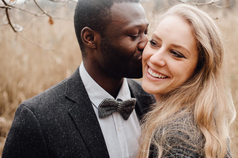 Ein Mann küsst seine Verlobte auf die Wange während sie glücklich lacht