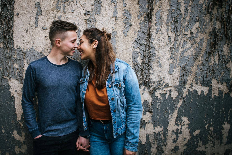 Love Story Shootin in Bonn, ein Paar schaut sich verliebt an während es an einer alten bewachsenen Wand steht.