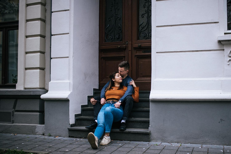 Ein Paar kuschelt auf einer Treppe beim Paarshooting in Bonn.