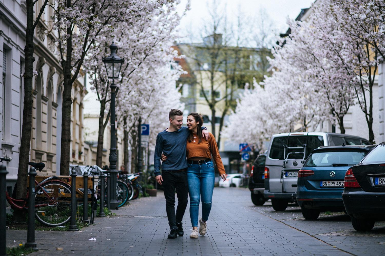 Ein Hand in Hand spazierendes Paar in der Bonner Altstadt beim Fotoshooting.