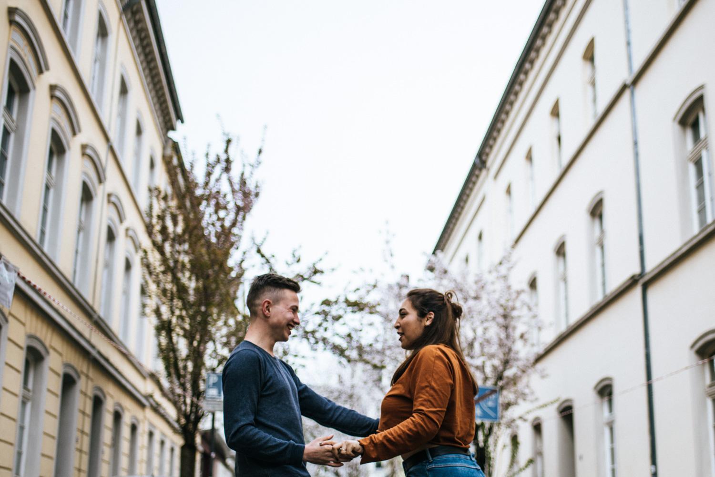 Ein Paar tanzt beim Fotoshooting zur kirschblüte in der Bonner Altstadt.