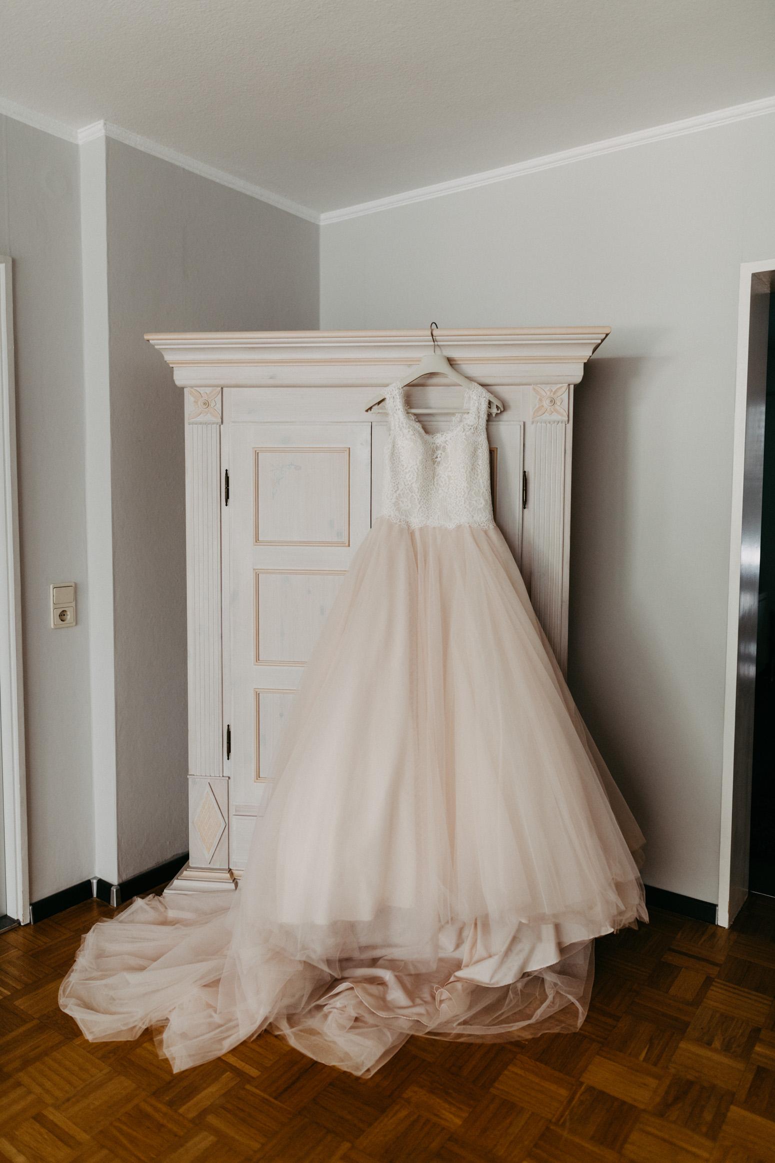 Ein Blush-Brautkleid hängt an einem antiken Schrank. Hochzeitsreportage von Daria Becker von Genuine Bonds aus Bonn