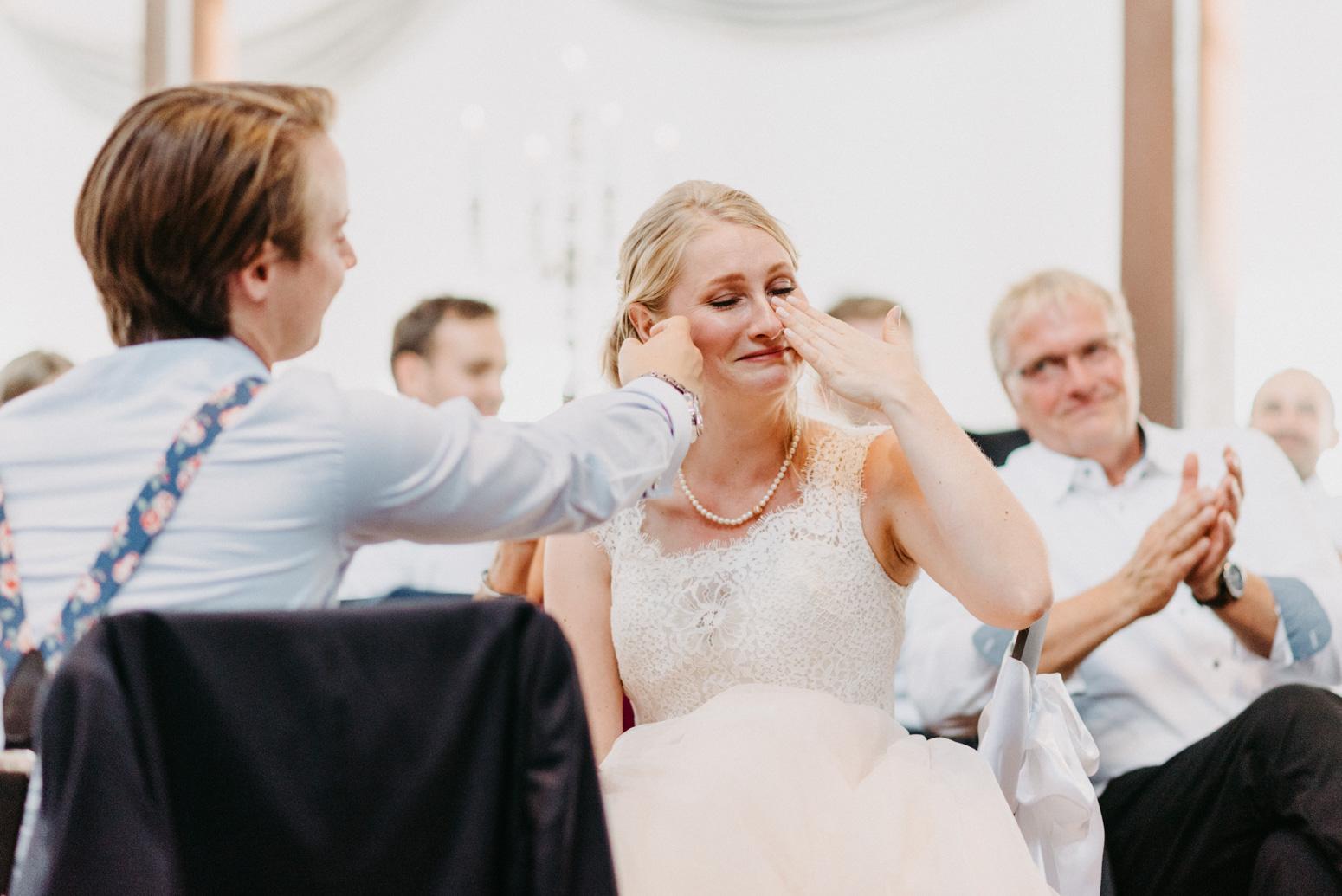 Die Braut weint vor Rührung während einer Rede. Hochzeitsfotografin in NRW Daria Becker von Genuine Bonds