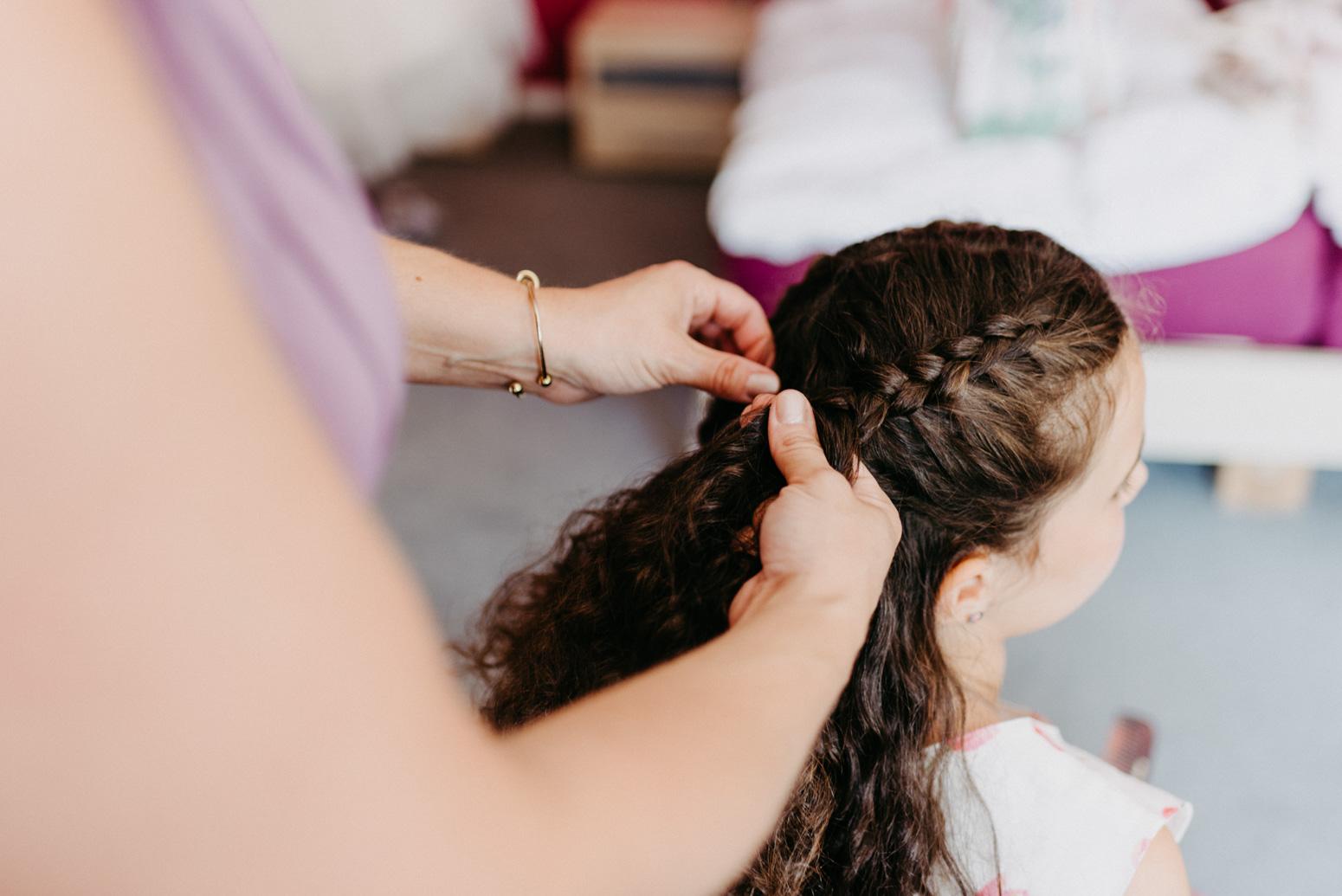 Haare flechten beim Getting Ready. Hochzeitsfotografin Daria Becker von Genuine Bonds aus Bonn