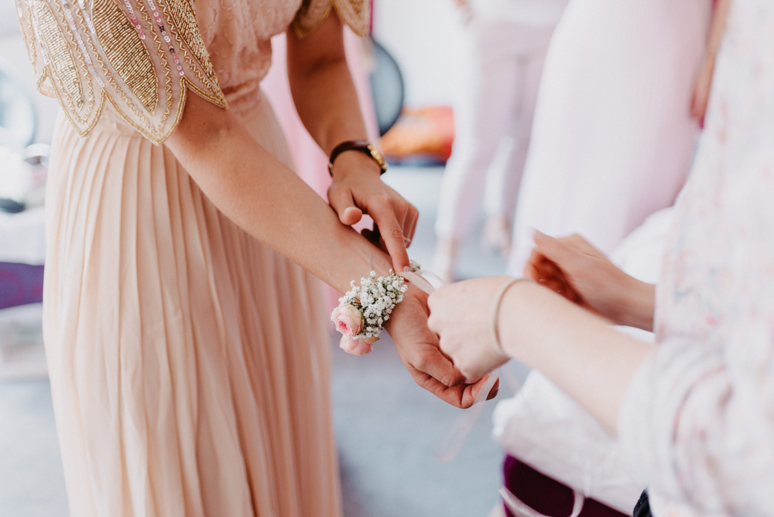 Braut bindet ihrer Trauzeugin ein Blumenarband um. Hochzeitsfotografin Daria Becker von Genuine Bonds aus Bonn
