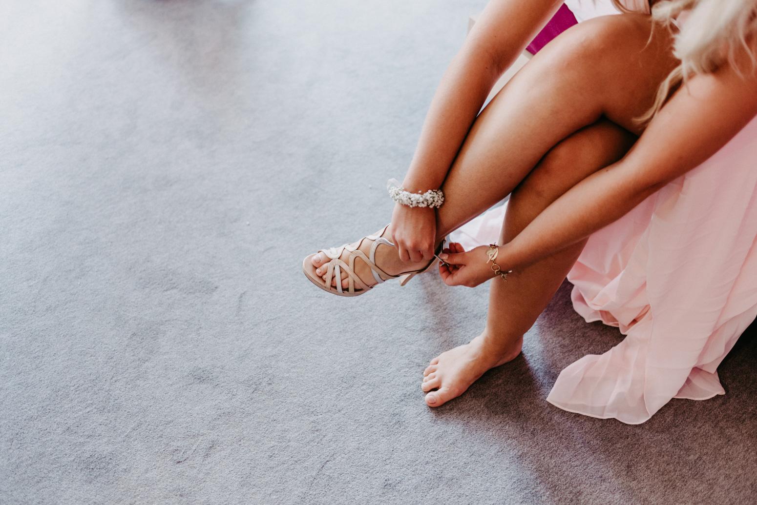 Brautjungfer zieht sich die High Heels an. Hochzeitsfotografin Daria Becker von Genuine Bonds aus Bonn