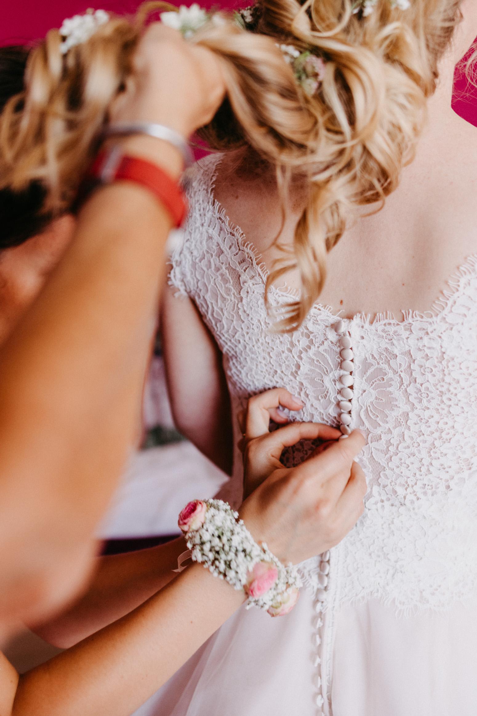 Zuknöpfen des Brautkleides. Hochzeitsfotografin Daria Becker von Genuine Bonds aus Bonn