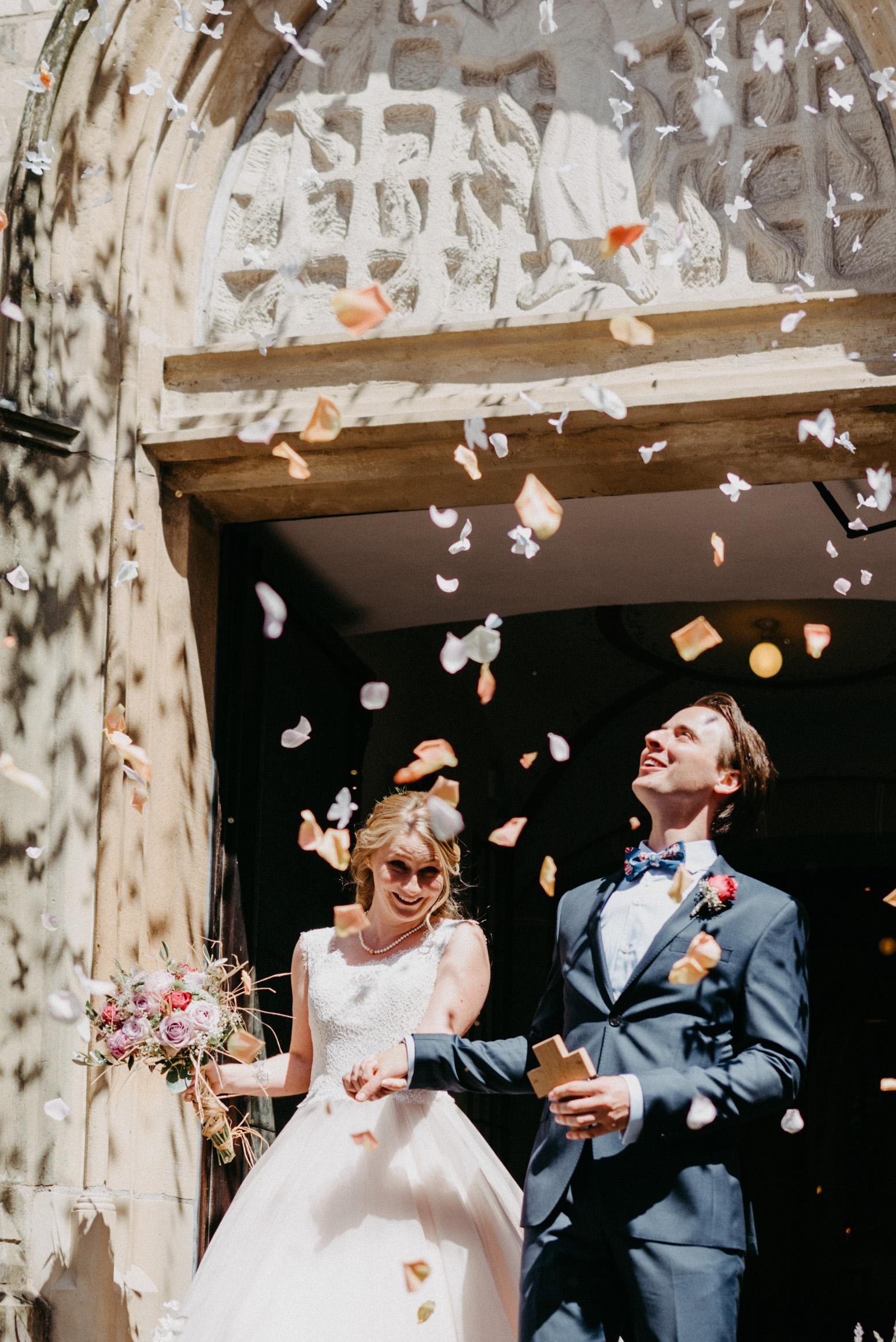 Auszug des Brautpaares aus der Kirche. Fliegendes Konfetti. Hochzeitsfotografin Daria Becker von Genuine Bonds aus Bonn