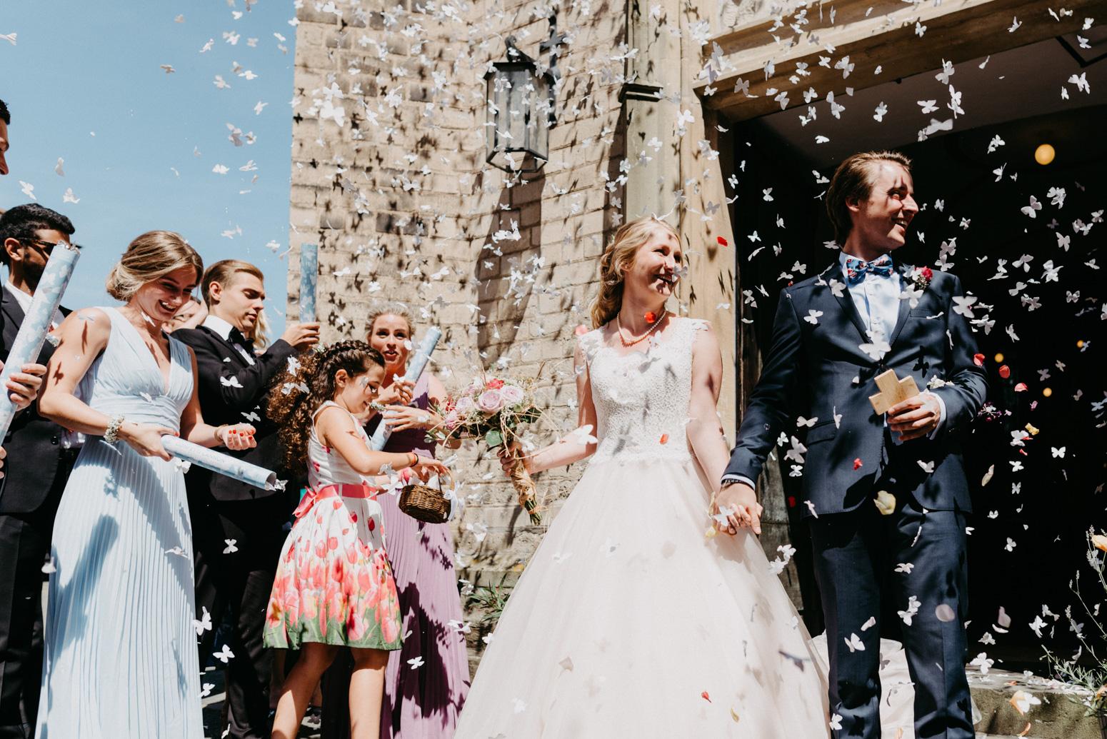 Fliegendes Konfetti beim Auszug des Brautpaares aus der Kirche. Hochzeitsfotografin Daria Becker von Genuine Bonds aus Bonn