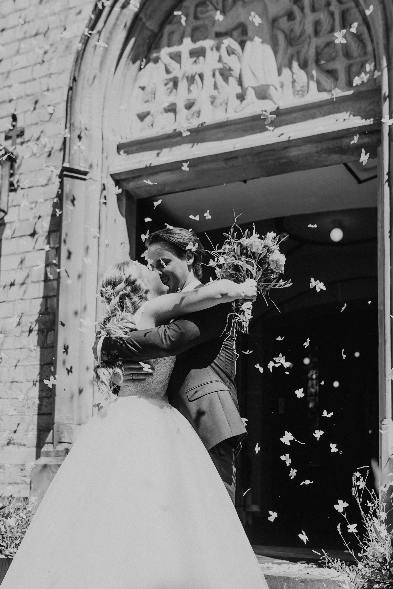Fliegendes Konfetti beim Auszug des Brautpaares aus der Kirche. Hochzeitsreportage Daria Becker von Genuine Bonds aus Bonn