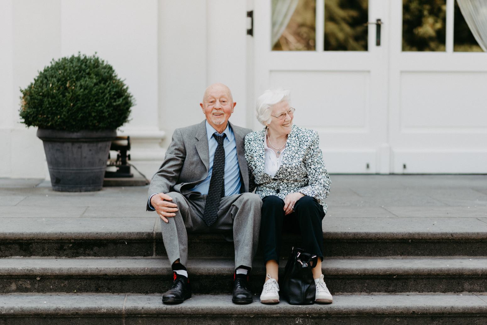Älteres Paar sitzt Arm in Arm auf einer Treppe.
