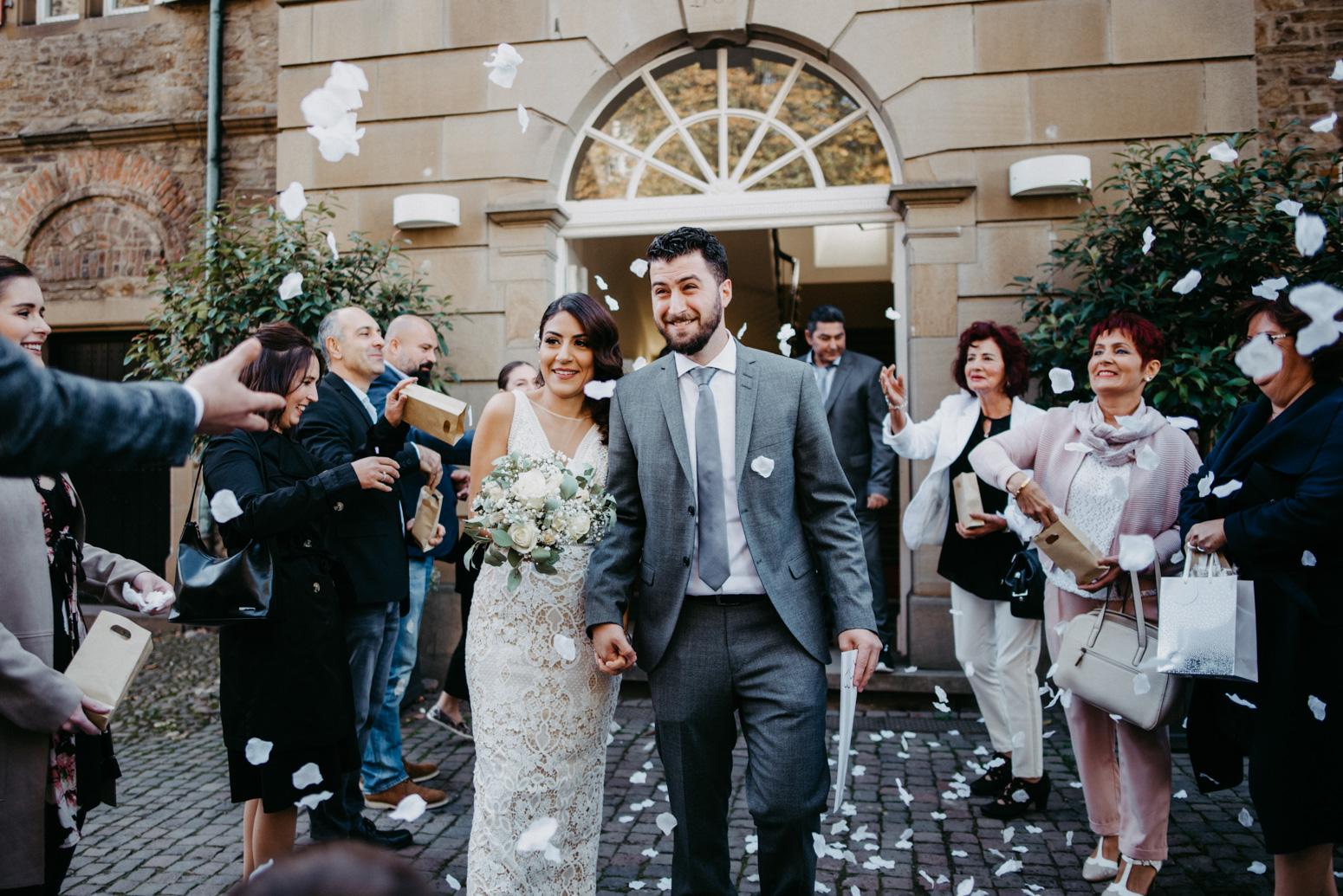 Auszug des Brautpaares aus dem Standesamt des Schloss Broich, Foto von der Hochzeitsfotografin Daria Becker von Genuine Bonds